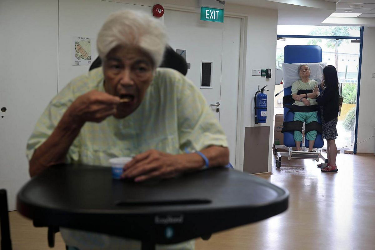 Mrs Gloria Amy Locke (left), 79, enjoys ice-cream on an easy stand during a physiotherapy session as Mdm Lim Leong Choo (right), 89 years old, is seen on a tilt table with a family relative. Both diagnosed with dementia, Mrs Locke had a fracture afte