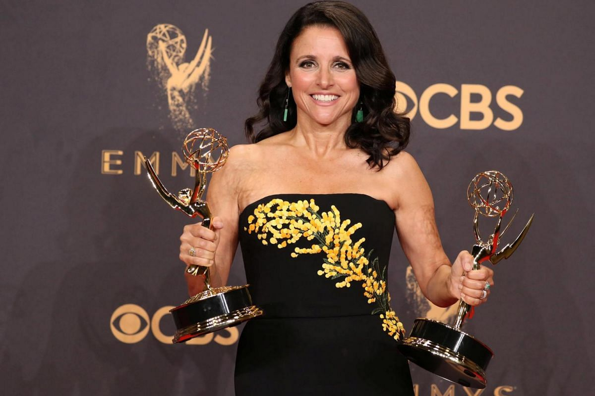 Julia Louis-Dreyfus holds her Emmys for Outstanding Lead Actress in a Comedy Series and Outstanding Comedy Series for Veep.