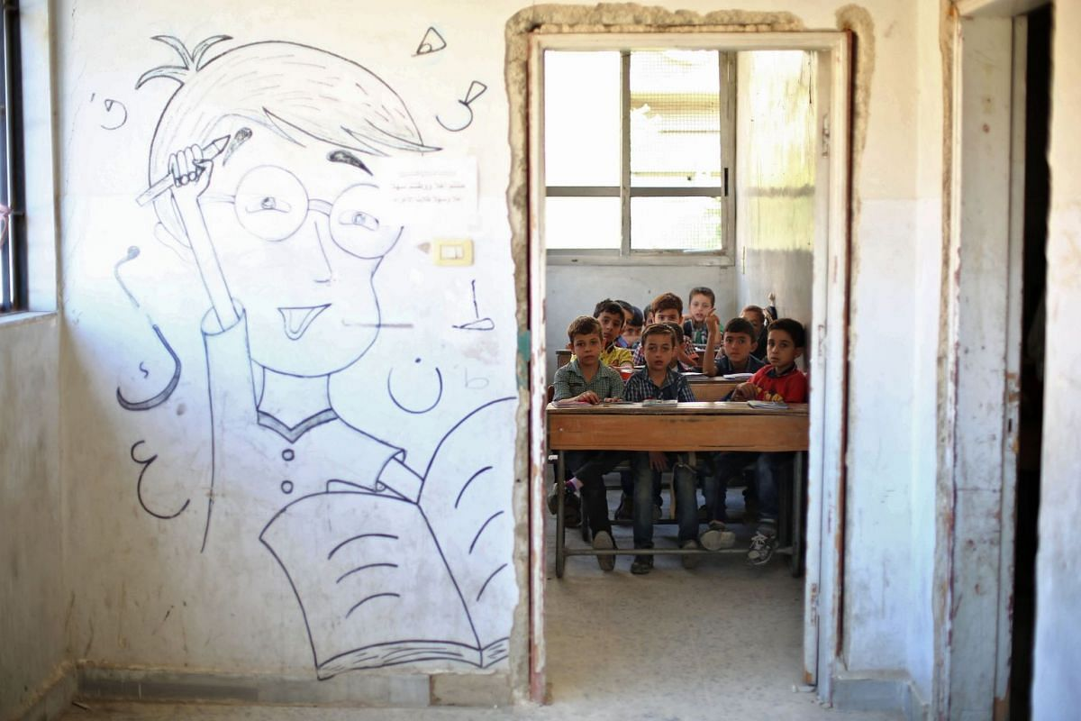 Syrian pupils sit at their classroom in a school in the rebel-held Eastern Ghouta town of Douma on Sept 18, 2017. Syria's six-year conflict has ravaged its infrastructure and caused losses to its economy of $226 billion, according to estimates publis