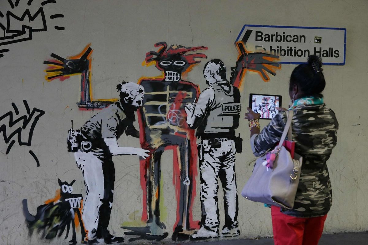 People take photographs of recently painted graffiti artworks by the street artist Banksy, in London on Sept 18, 2017. Street artist Banksy paid tribute to Jean-Michel Basquiat with two new murals in London near a major exhibition of the late US arti