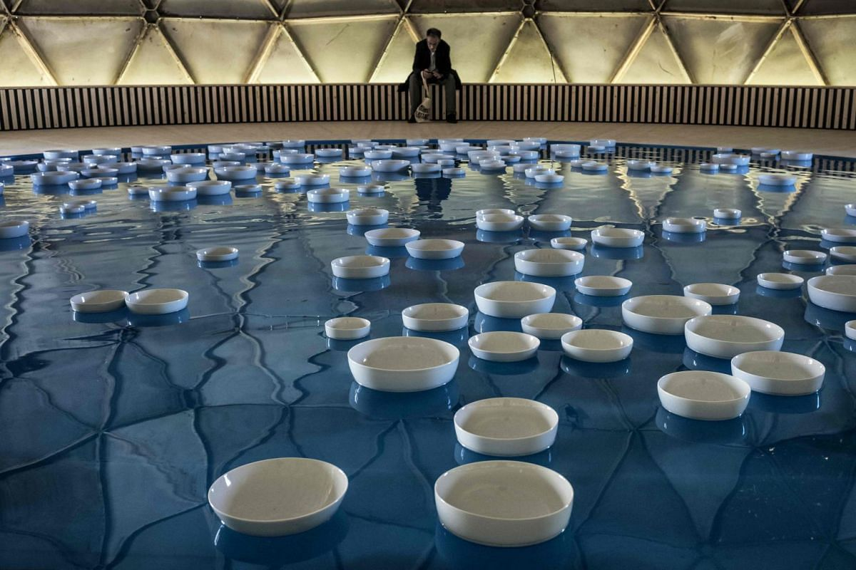 """A man sits to look at French artist Celeste Boursier-Mougenot's artwork """"clinamen v2"""" in Lyon on Sept 18, 2017, prior to the 14th Biennial of Contemporary Art of Lyon. PHOTO: AFP"""