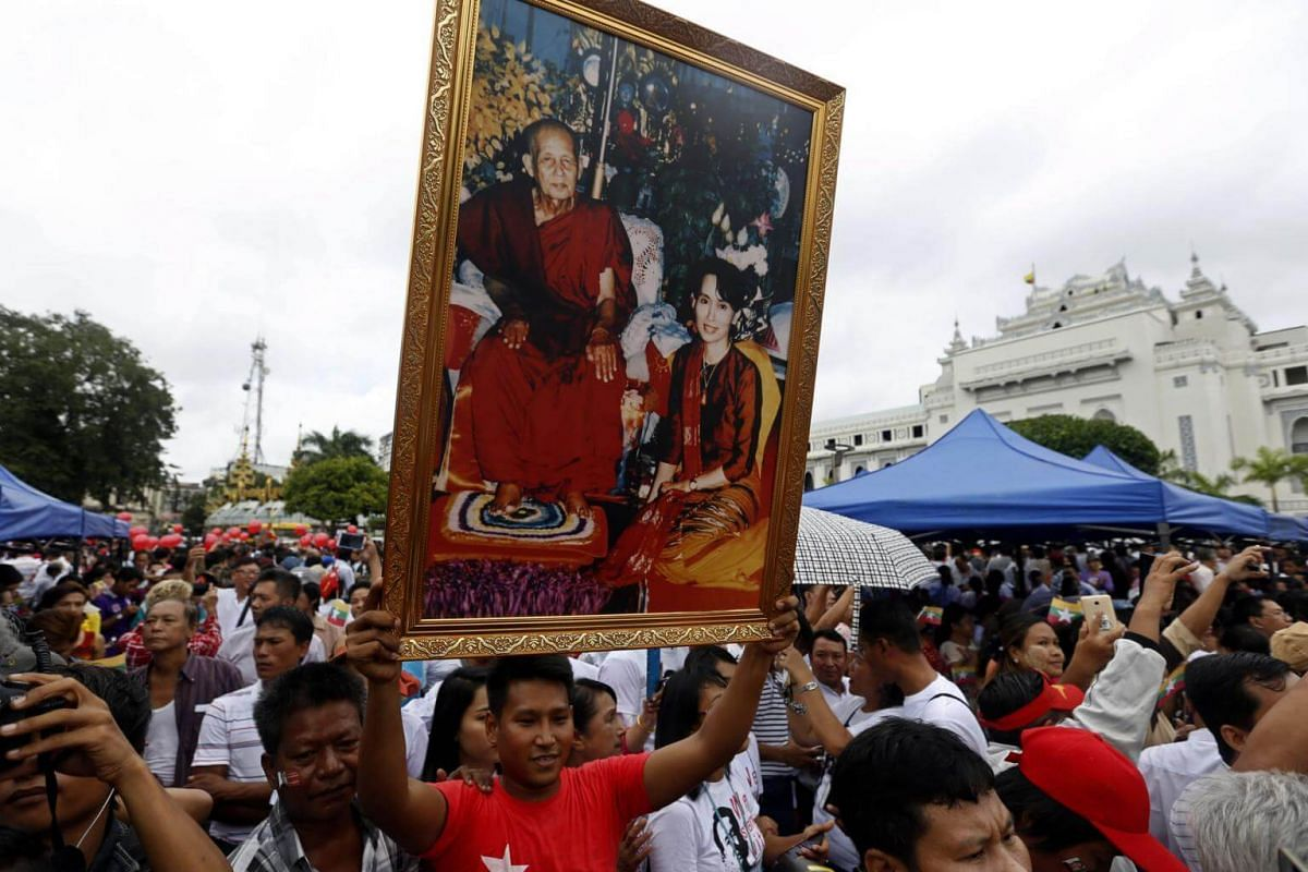 A man holds a portrait of Myanmar State Counselor Aung San Suu Kyi and late Buddhist monk ThaMaNya Sayardaw as he attends a public gathering held to listen to the live speech, on Sept 19, 2017.
