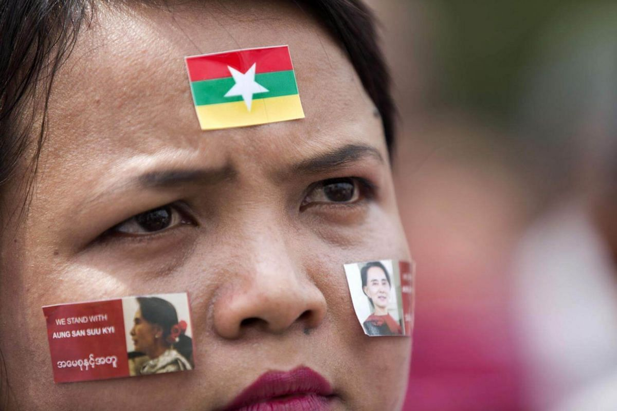 A woman wears stickers with the image of Aung San Suu Kyi on her cheeks as she attends a broadcast of the live speech in front of City Hall in Yangon, on Sept 19, 2017.