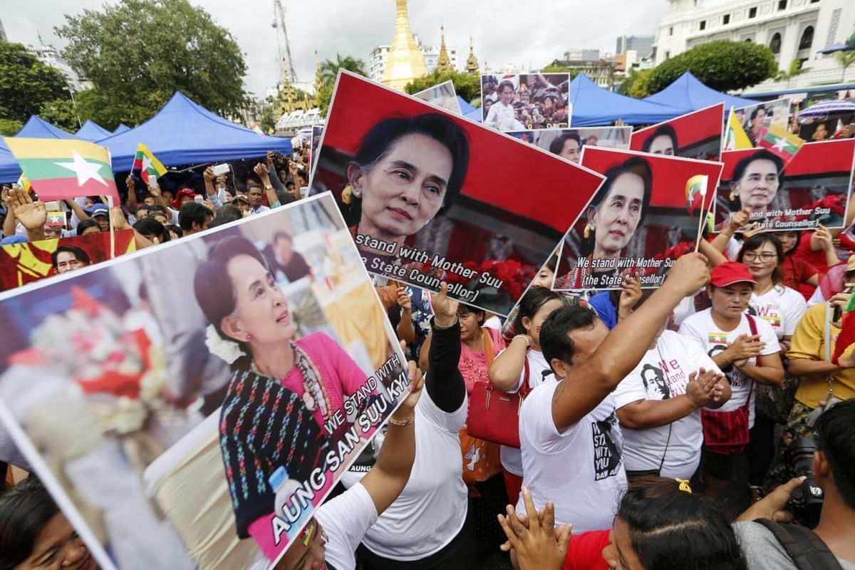 Myanmar citizens hold images of Myanmar State Counselor Aung San Suu Kyi as they attend a public gathering held to listen to her speech, on Sept 19, 2017.