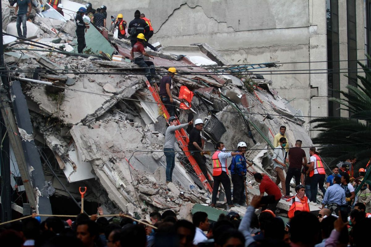 Rescuers and volunteers remove rubble and debris from a flattened building in search of survivors after a powerful quake in Mexico City on September 19, 2017. PHOTO: AFP