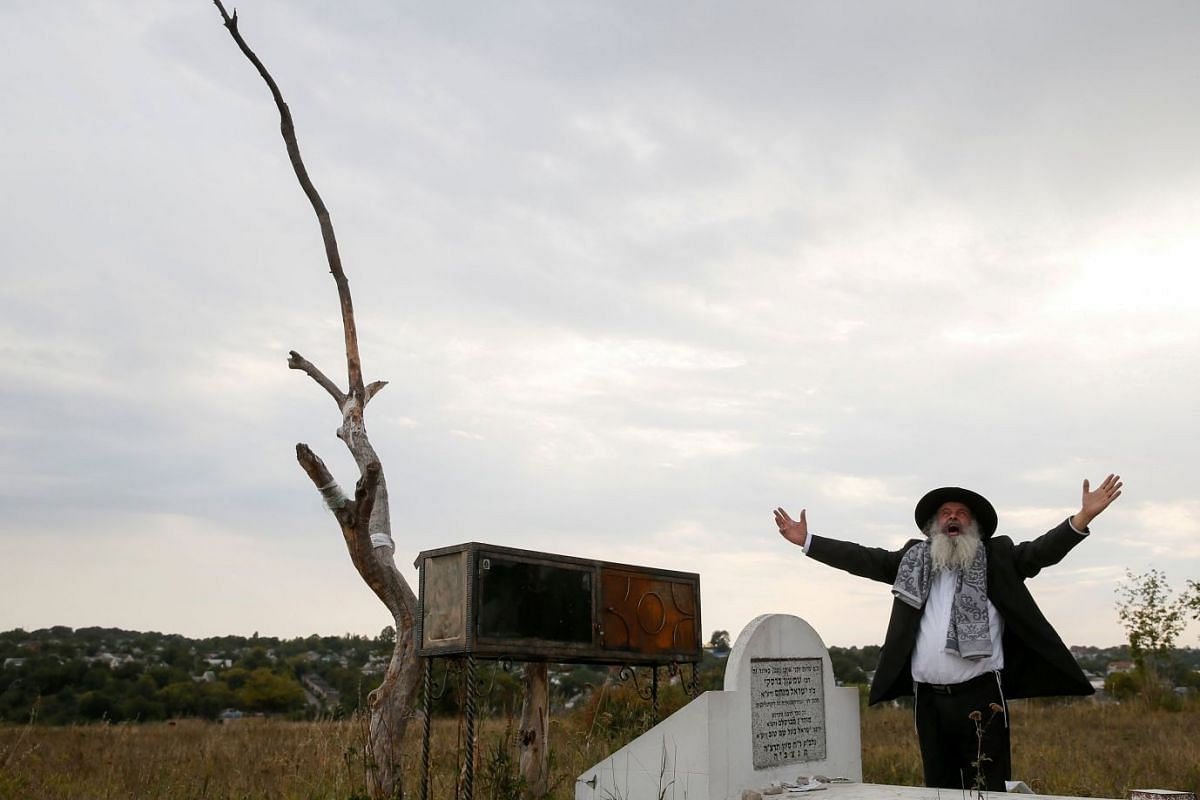 An ultra-Orthodox Jewish pilgrim prays next to a tomb at an old Jewish cemetery on the eve of Rosh Hashanah holiday, the Jewish New Year, in the town of Uman, Ukraine September 19, 2017. PHOTO: REUTERS