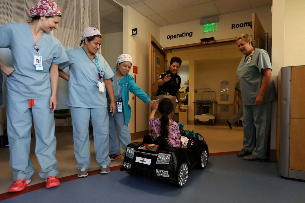 Andrea Destraio, 5, slaps hands with medical staff and invited police officers whose charity donated to Rady Children's Hospital to start a program that uses remote control cars to take young patients to the operating room, in San Diego, California,