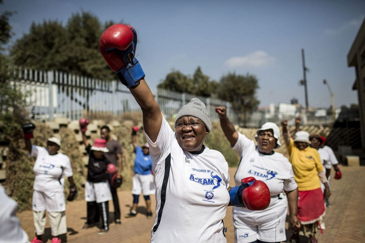 """The """"Boxing Gogos"""" (Grannies) stretch as they take part in a session hosted by the """"A Team Gym"""" in Cosmo City in Johannesburg on September 19, 2017. The grandmothers, many of whom are over 70 have been training with coach Claude Maphosa and claim"""
