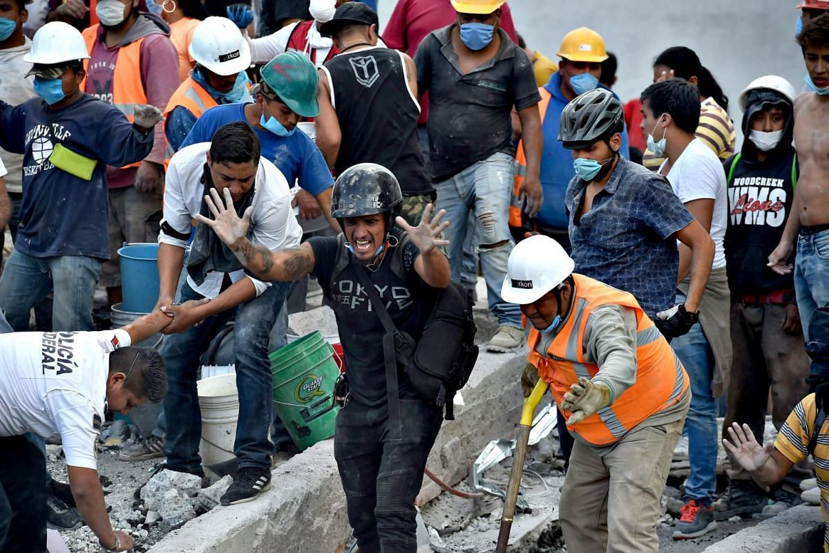 Rescuers, firefighters, policemen, soldiers and volunteers remove rubble and debris from a flattened building in search of survivors.