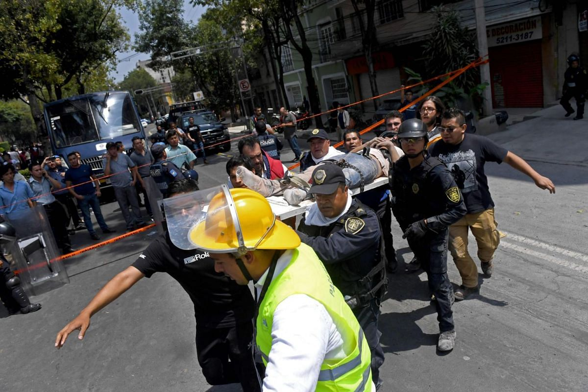 Rescuers carrying a wounded person after a quake in Mexico City, on Sept 19, 2017.