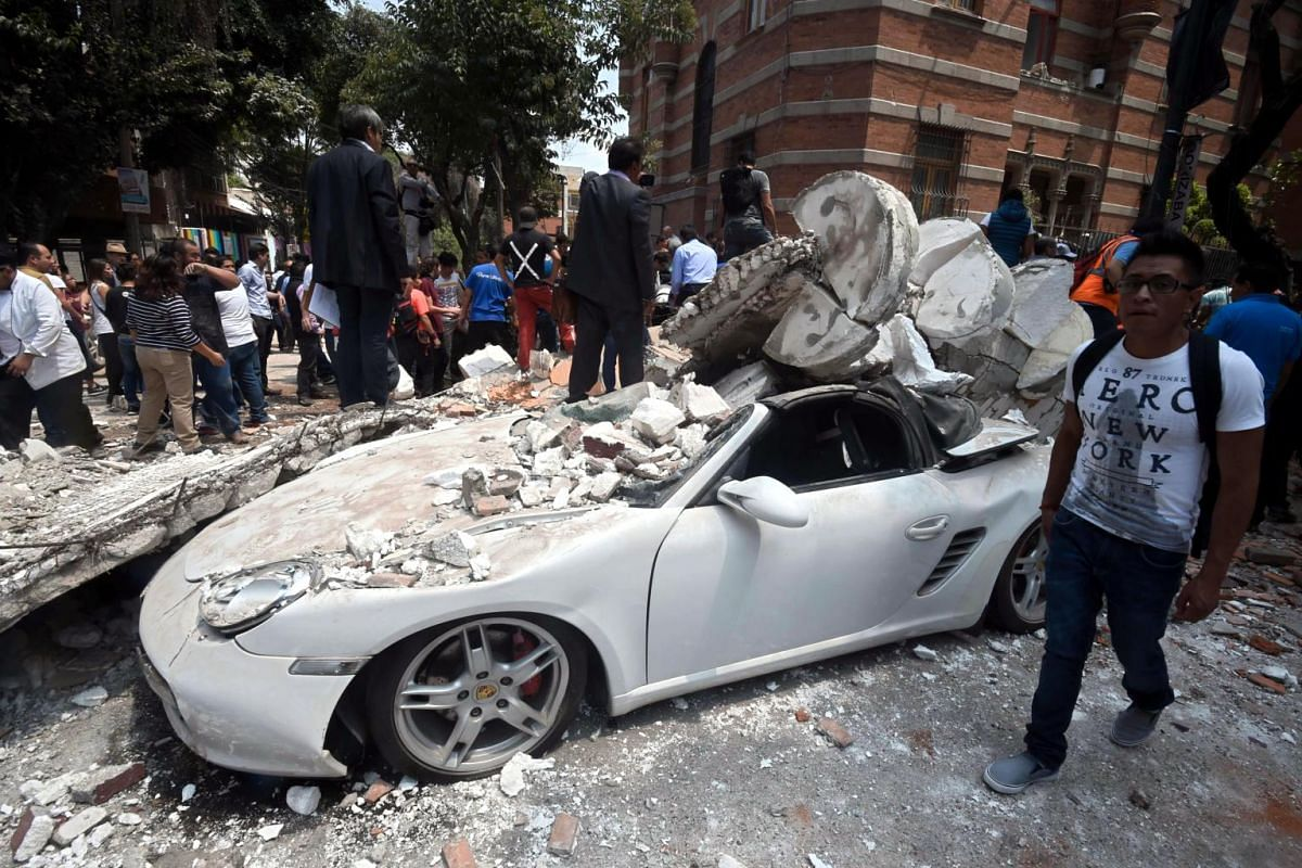 A man stands next to a car crashed by debris from a damaged building after a quake rattled Mexico City, on Sept 19, 2017.