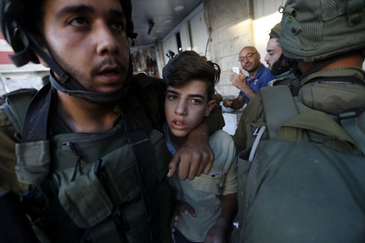Israeli army soldiers arrest a Palestinian (C) following scuffling during raids in the West Bank city of Hebron, September 20, 2017. PHOTO: EPA-EFE