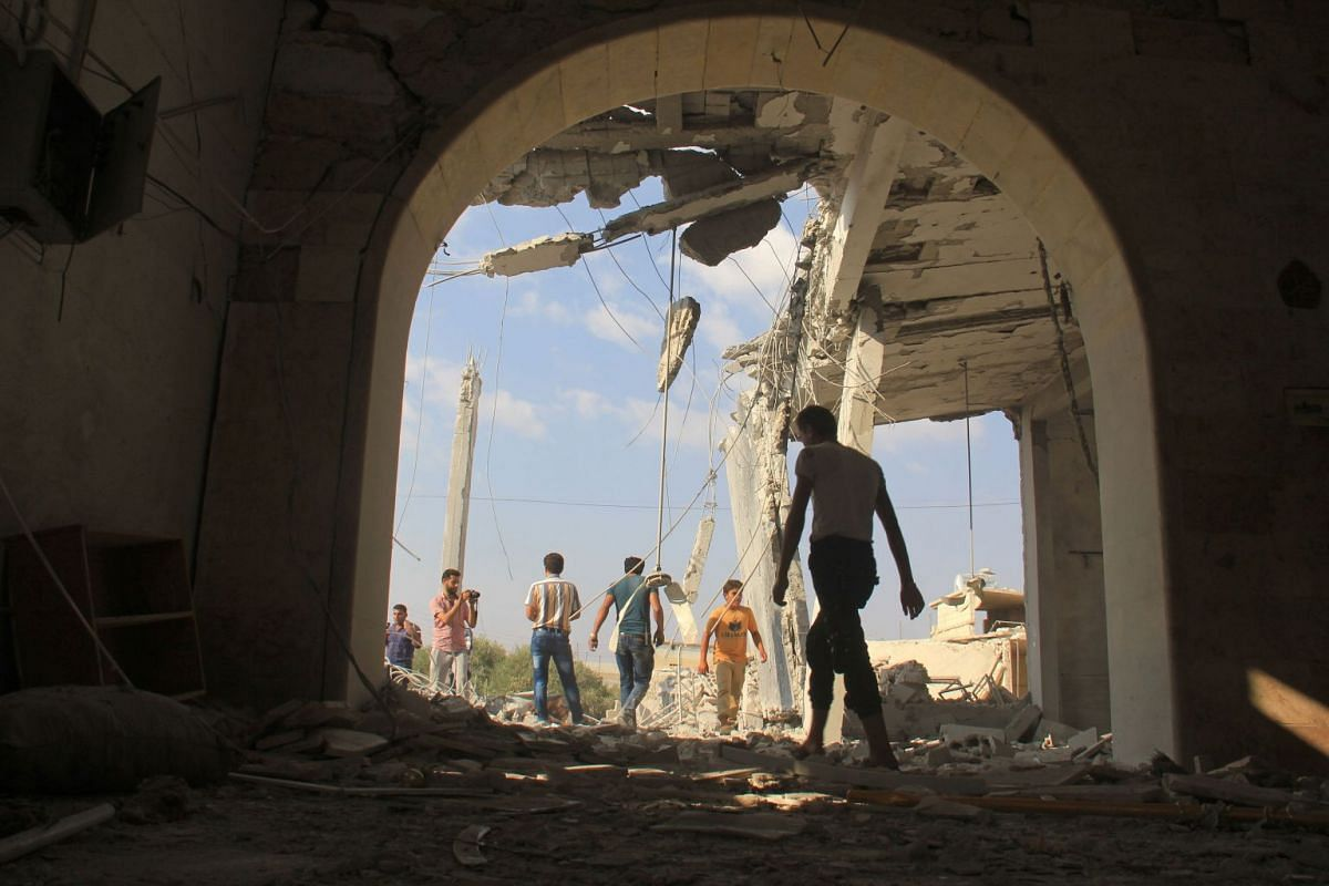 Syrians check the damage in a mosque following a reported air strike on the village of Jarjanaz, in the Maaret al-Numan district of Syria's Idlib province, on September 20, 2017. PHOTO: AFP