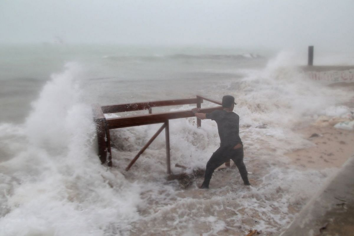 A man tries to salvage a table belonging to his restaurant before the arrival of Hurricane Maria in Punta Cana, Dominican Republic, on Sept 20, 2017.