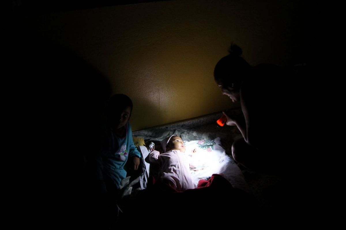 A woman with a flashlight illuminates her baby inside a shelter before the arrival of the Hurricane Maria in Punta Cana on Sept 20, 2017.