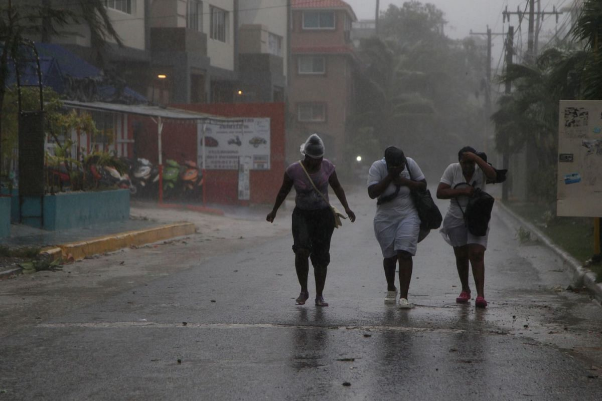Women walk against the wind before the arrival of Hurricane Maria in Punta Cana, Dominican Republic, on Sept 20, 2017.