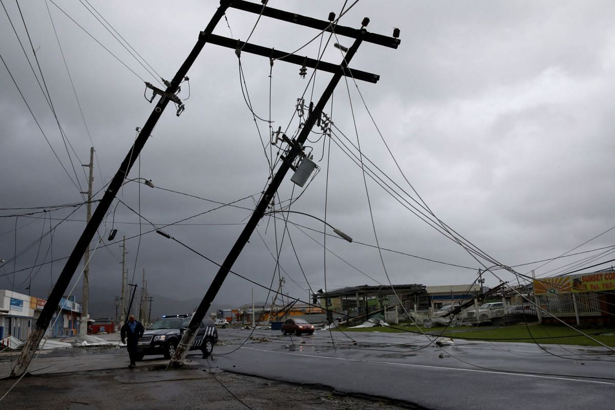 A police officer walks next to damaged electrical installations after the area was hit by Hurricane Maria en Guayama, Puerto Rico on Sept 20, 2017.