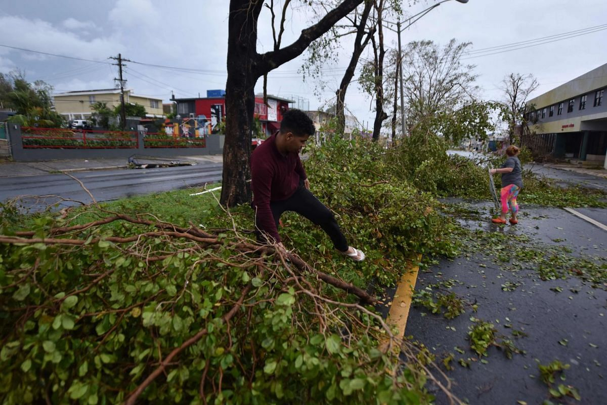 Residents clear fallen debris after the passage of Hurricane Maria, in San Juan, Puerto Rico, on Sept 20, 2017.
