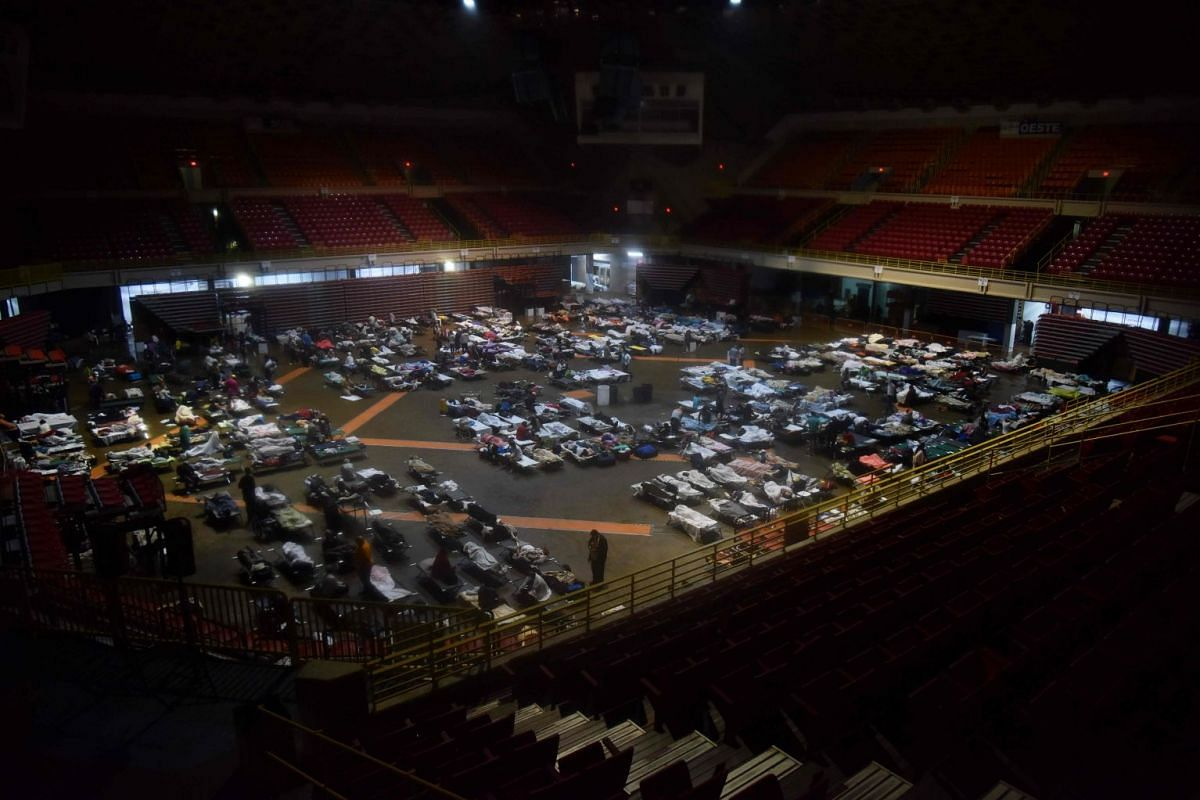 Residents seek shelter inside Roberto Clemente Coliseum in San Juan, Puerto Rico, early on Sept 20, 2017, as Hurricane Maria passes the island.