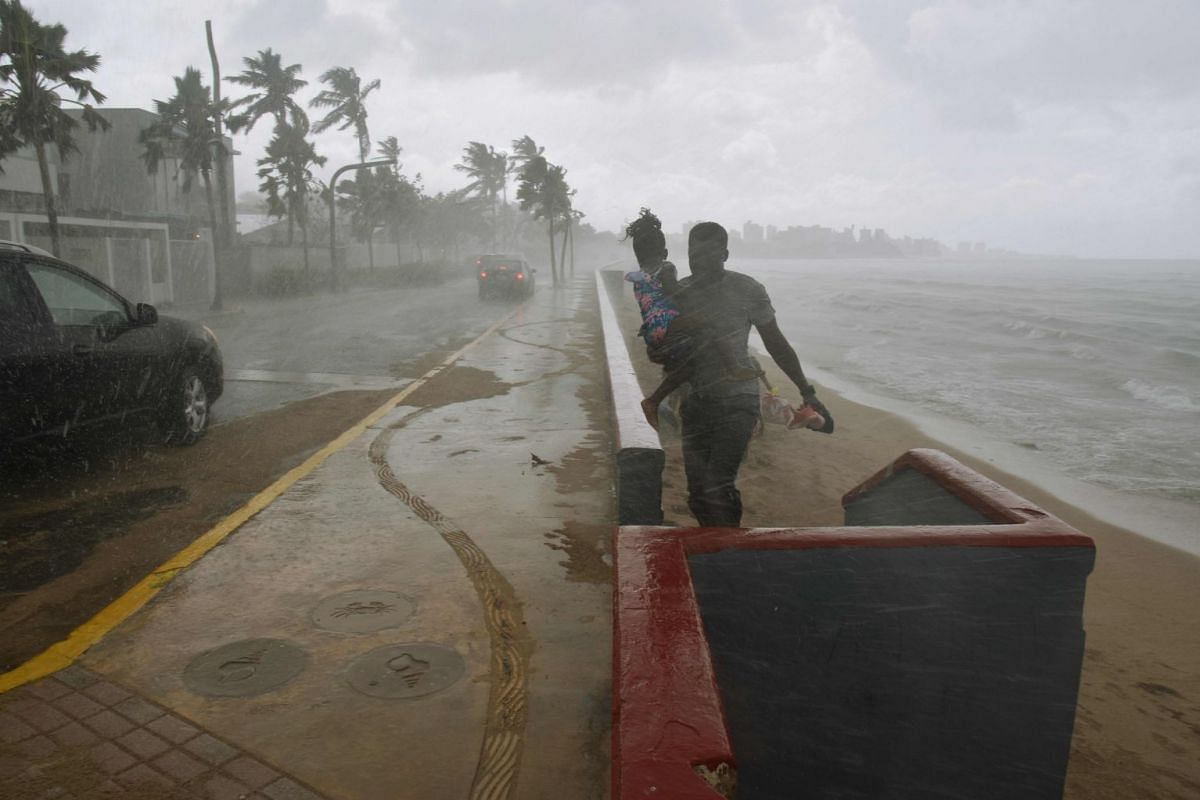 A man and his daughter flee from the rain on a beach in San Juan, Puerto Rico, on Sept 19, 2017, prior to the arrival of Hurricane Maria.