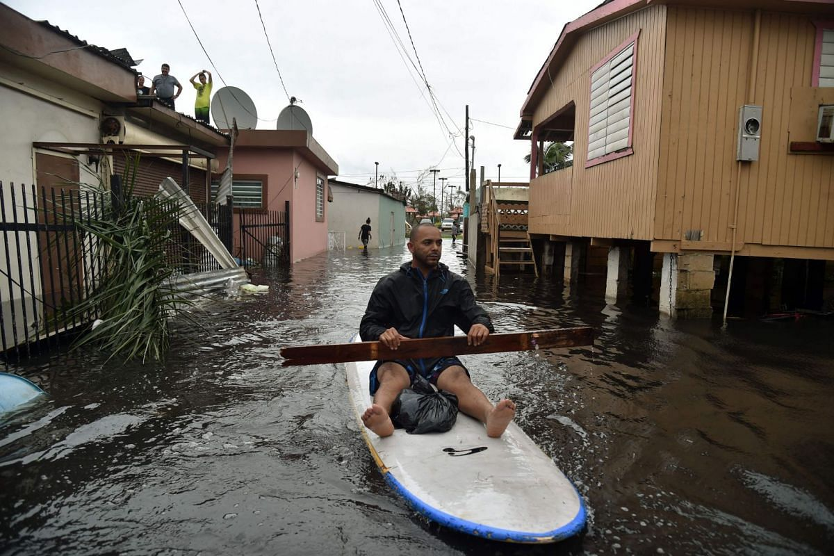 A man uses a stand up paddle board to row down a street flooded by Hurricane Maria in Juana Matos, Catano, Puerto Rico, on September 21, 2017. PHOTO: AFP
