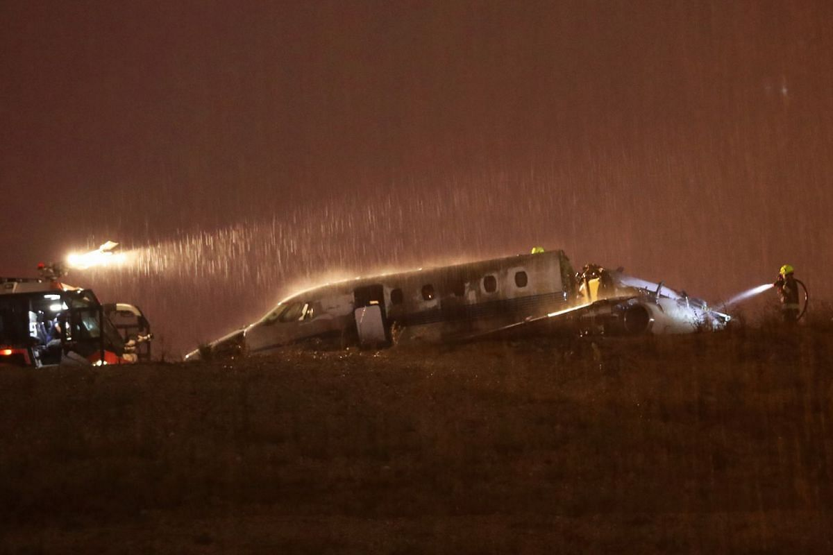Firefighters stand next to the wreckage of a private jet after it crashed at Ataturk airport in Istanbul, Turkey, September 21, 2017. PHOTO: REUTERS