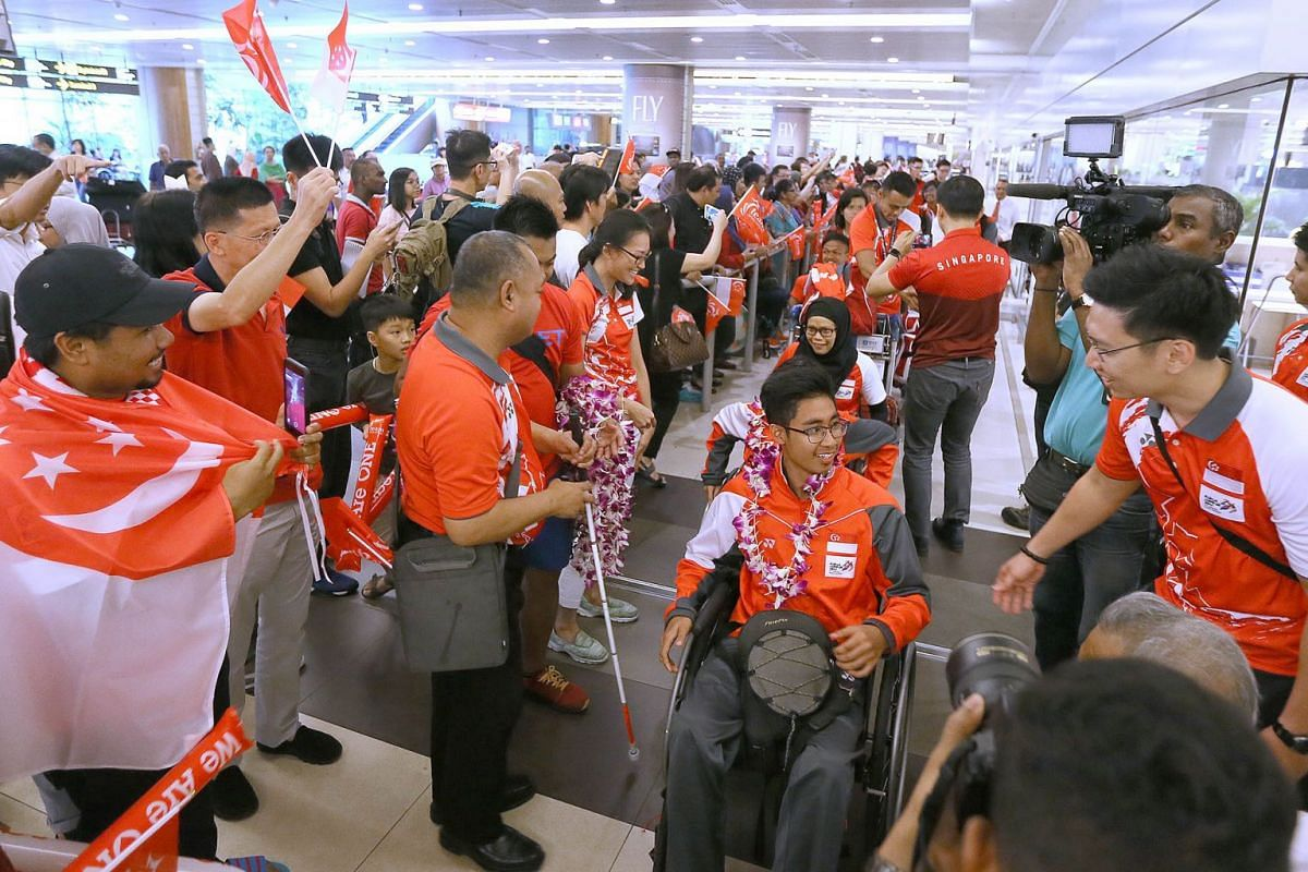 Wheelchair racer Shahrul Izwan being given a rousing welcome at Changi Airport's Terminal 2 along with his 2017 Asean Para Games teammates when the Team Singapore contingent returned home on 24 September, 2017. The para- athletes achieved Singapore