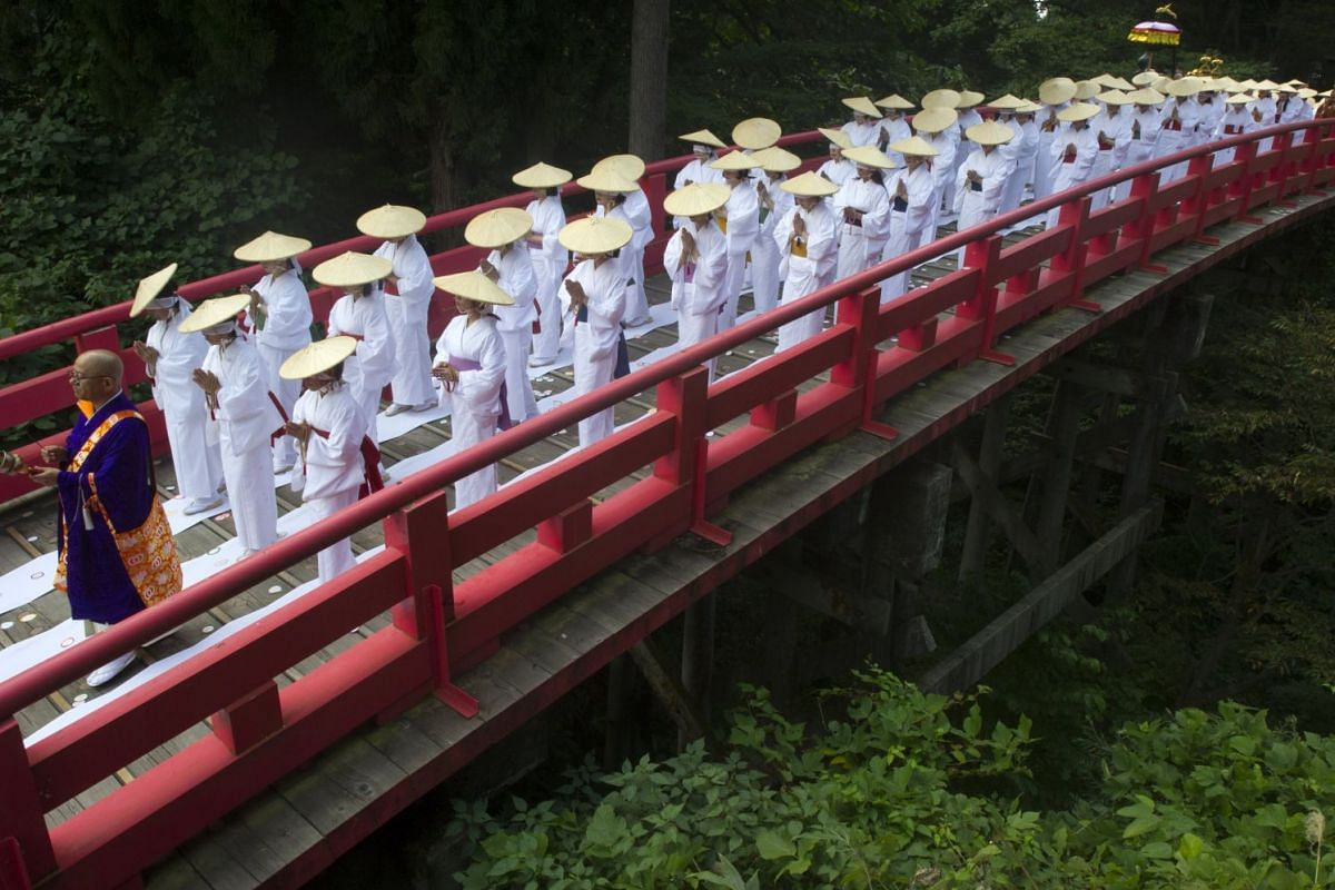 Blindfolded Japanese women participants walk across a red bridge during the 'Purification Ceremony on the Cloth Bridge', or Nunobashi Kanjoe ceremony in Japanese, in Tateyama city, Toyama prefecture, Japan, 24 September 2017. Only females and Buddhis