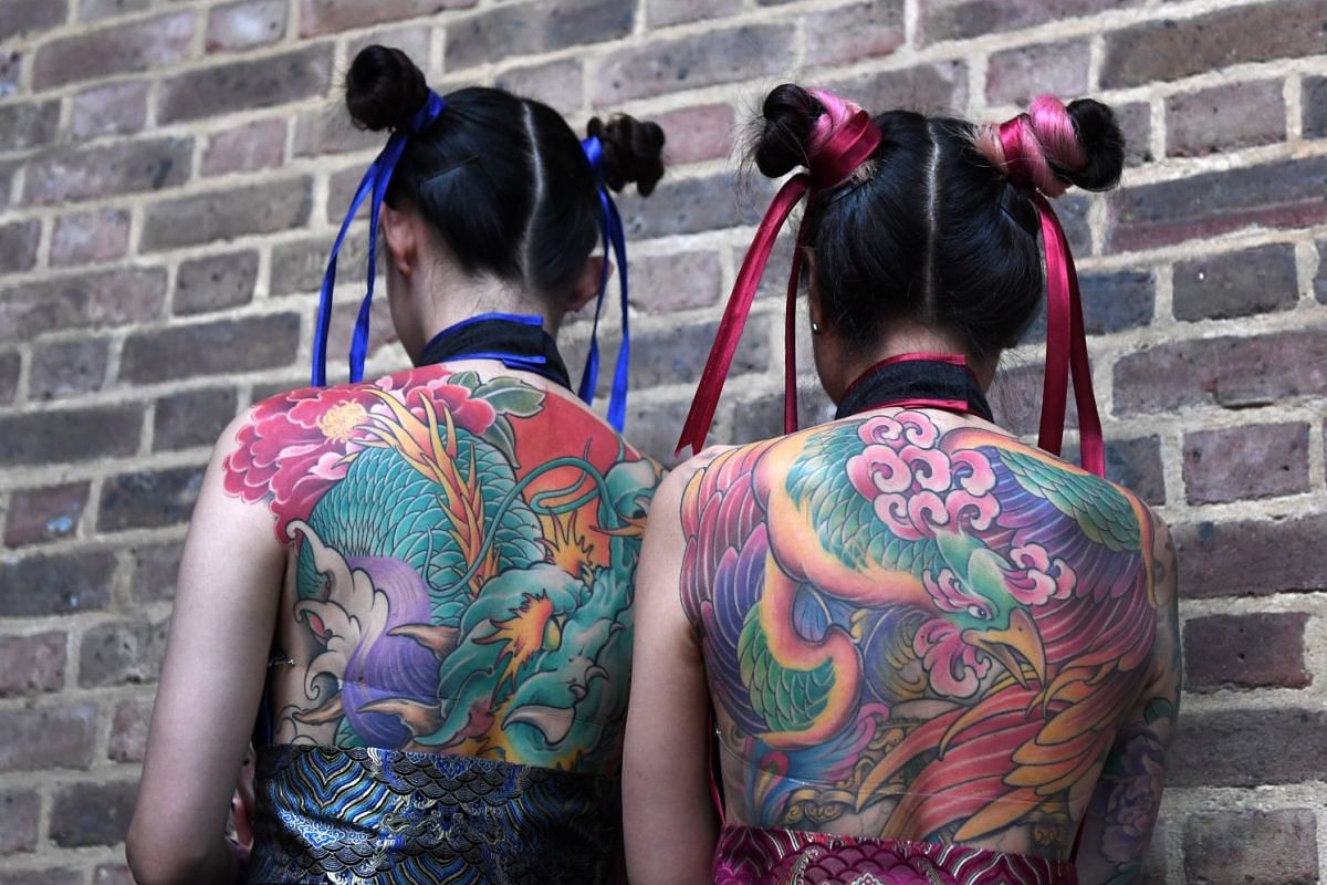 Tattoo enthusiasts pose for photographs during the London Tattoo Convention at the Tobacco Docks, in London, Britain, 24 September 2017. PHOTO: EPA-EFE