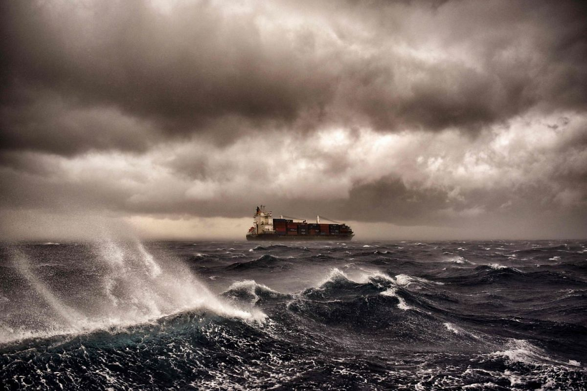A cargo ship sails on the Mediterranean sea during a thunderstorm some 20 naughtical miles from Malta on September 24, 2017. PHOTO: AFP