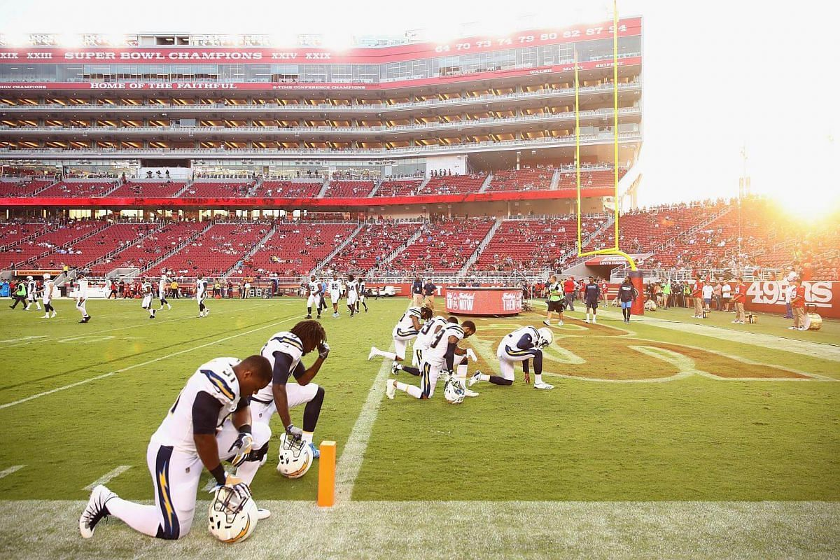 Players from the Los Angeles Chargers kneel during the US national anthem before an NFL game against the San Francisco 49ers on Aug 31, 2017.