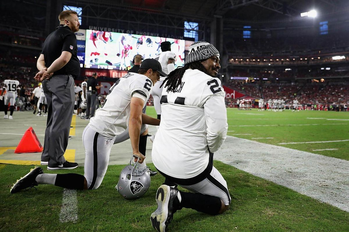 Running back Marshawn Lynch (#24) and kicker Giorgio Tavecchio (#2) of the Oakland Raiders kneel during the US national anthem before an NFL game against the Arizona Cardinals on Aug 12, 2017.