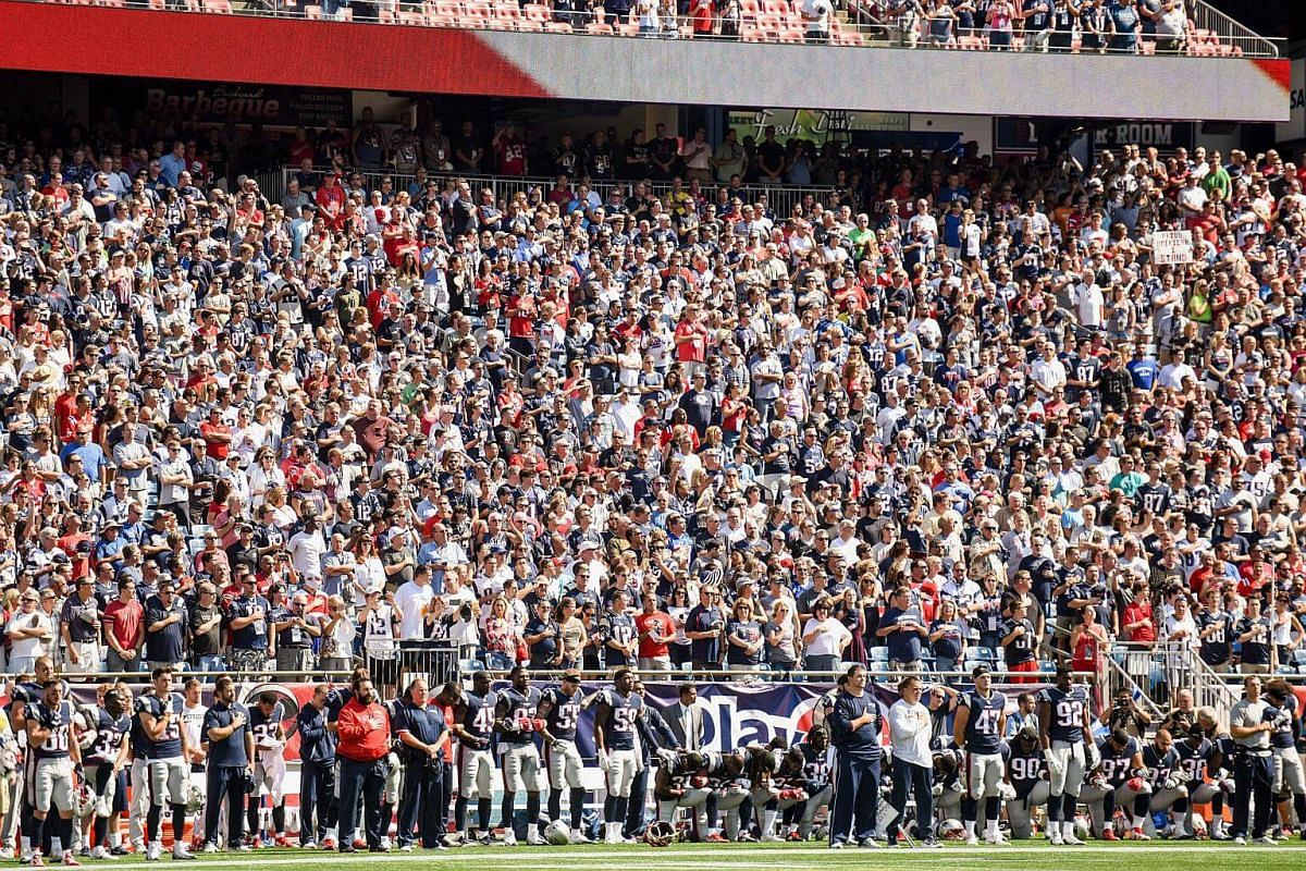 New England Patriots players hold hands and kneel during the US national anthem before an NFL game against the Houston Texans on Sept 24, 2017.