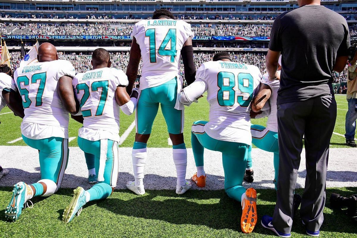 Laremy Tunsil (#67), Maurice Smith (#27) and Julius Thomas (#89) kneel with Jarvis Landry (#14) of the Miami Dolphins during the US national anthem before an NFL game against the New York Jets on Sept 24, 2017.