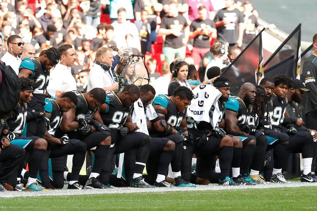 Jacksonville Jaguars players kneel during the US national anthem before an NFL game against the Baltimore Ravens on Sept 24, 2017.