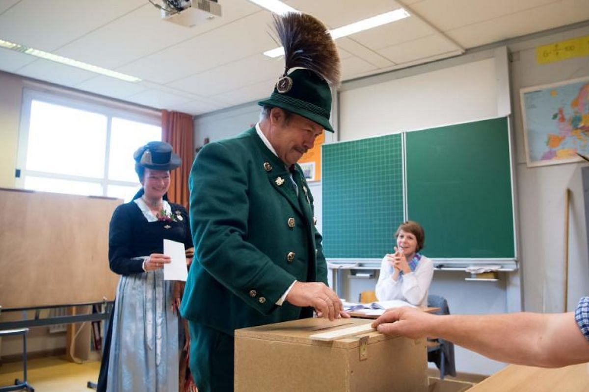 A man and a woman in traditional Bavarian dress cast their ballots at a polling station in Unterwoessen, southern Germany on Sunday (Sept 24).