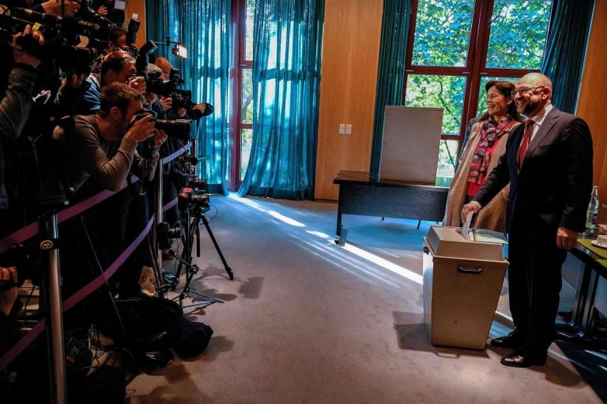 Martin Schulz, leader of Germany's social democratic SPD party and candidate for Chancellor, and his wife Inge Schulz cast their ballots at a polling station in Wuerselen, western Germany.