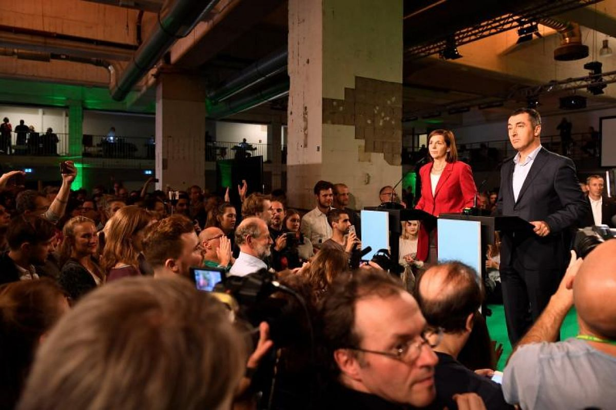 Greens party top candidates Cem Ozdemir (right) and Katrin Goering-Eckardt  react to the first prediction of the election result.