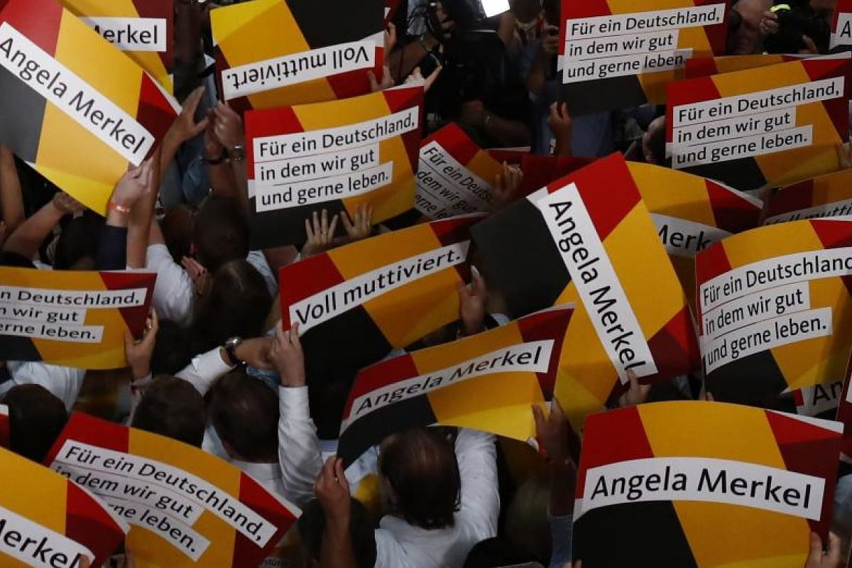 People hold placards while waiting for Christian Democratic Union party leader and German Chancellor Angela Merkel to react to the first exit polls.