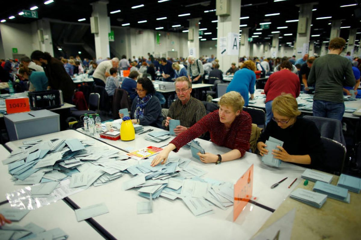Electoral officials sort ballot papers after the conclusion of voting.