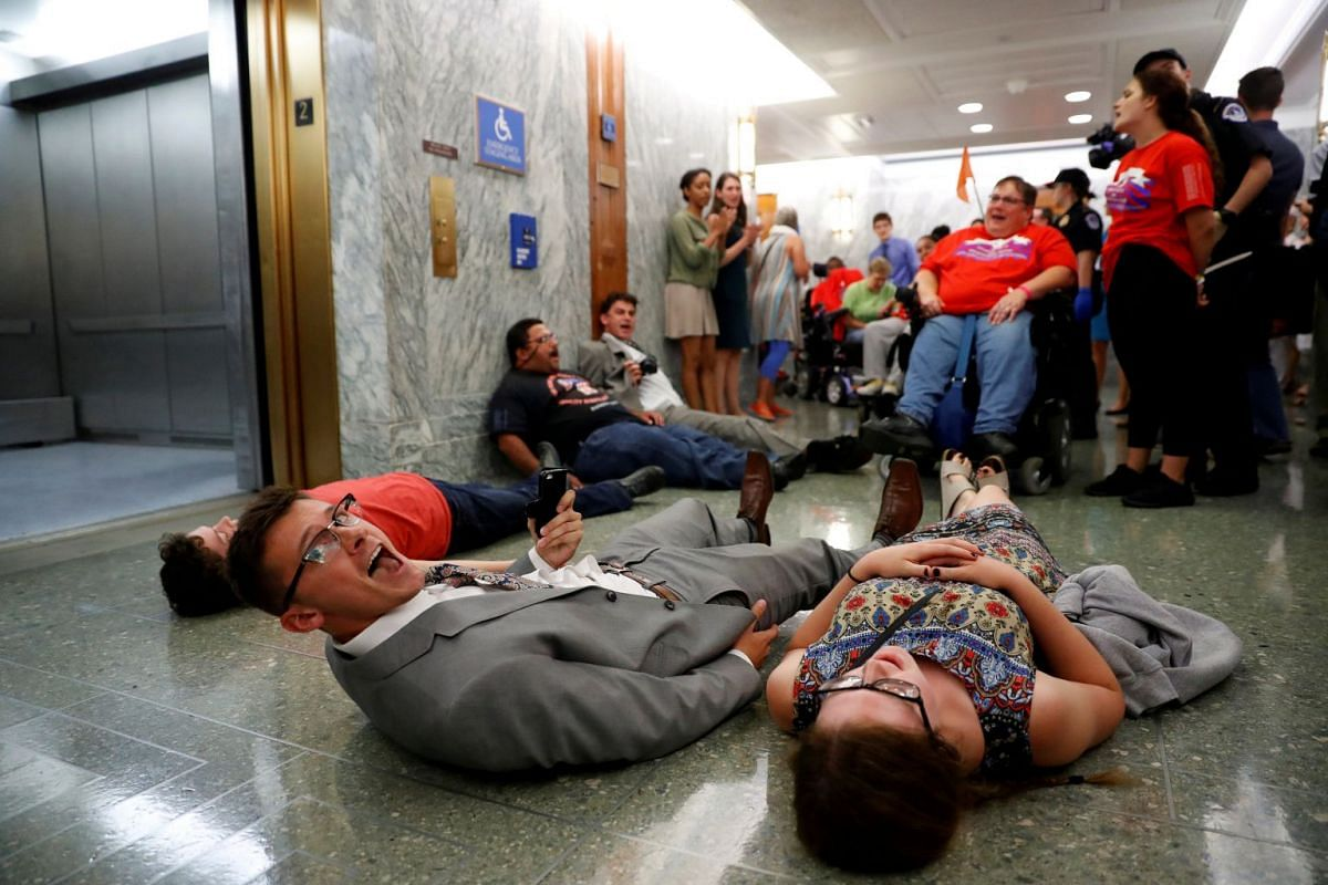 Demonstrators lie on the ground as the Senate Finance Committee holds a hearing on the latest Republican Effort to repeal and replace the Affordable Care Act on Capitol Hill in Washington DC.