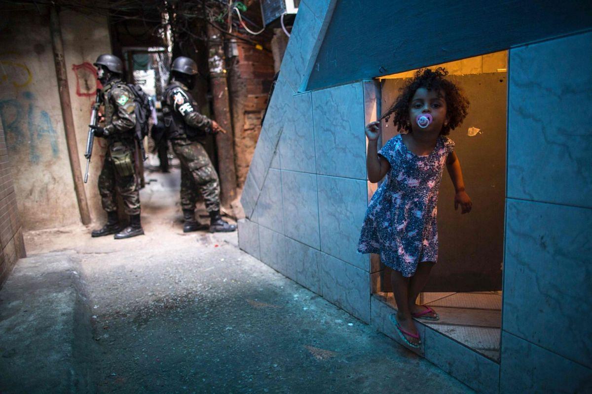 Employing urban combat tactics, Brazilian army military police personnel patrol along an alley in the Rocinha favela in Rio de Janeiro, Brazil on Sept 25, 2017. Security officials said the giant Rocinha favela in Rio de Janeiro was back under control