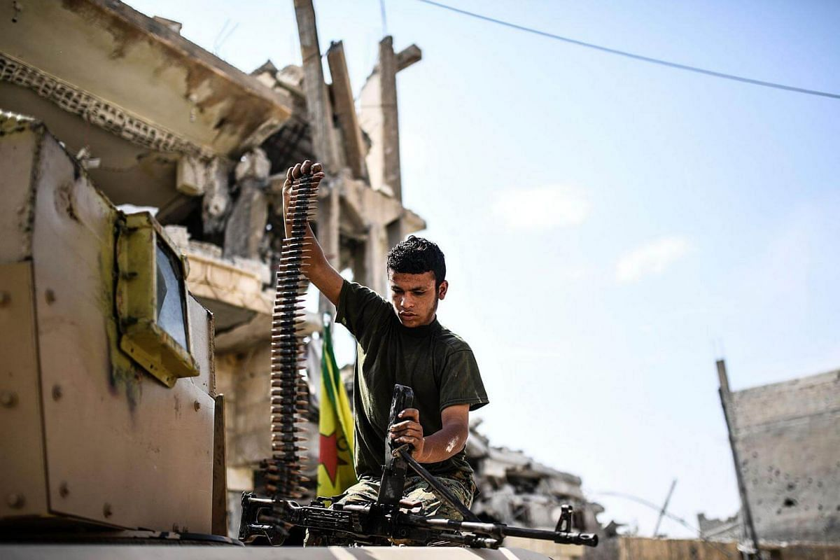 A member of the Syrian Democratic Forces loads a machine gun on the eastern frontline of Raqa on Sept 24, 2017.