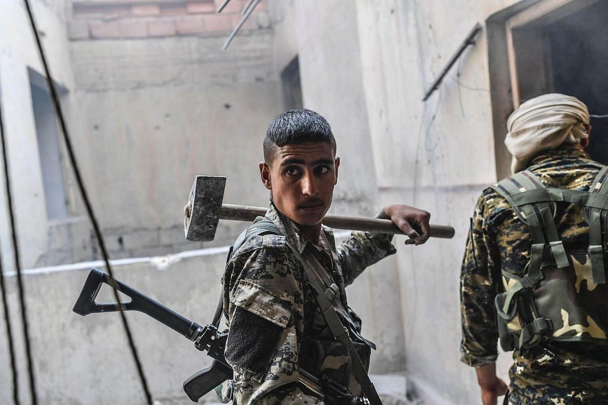 Members of the Syrian Democratic Forces check a house as they advance to the next building on the eastern frontline in Raqa on Sept 25, 2017.