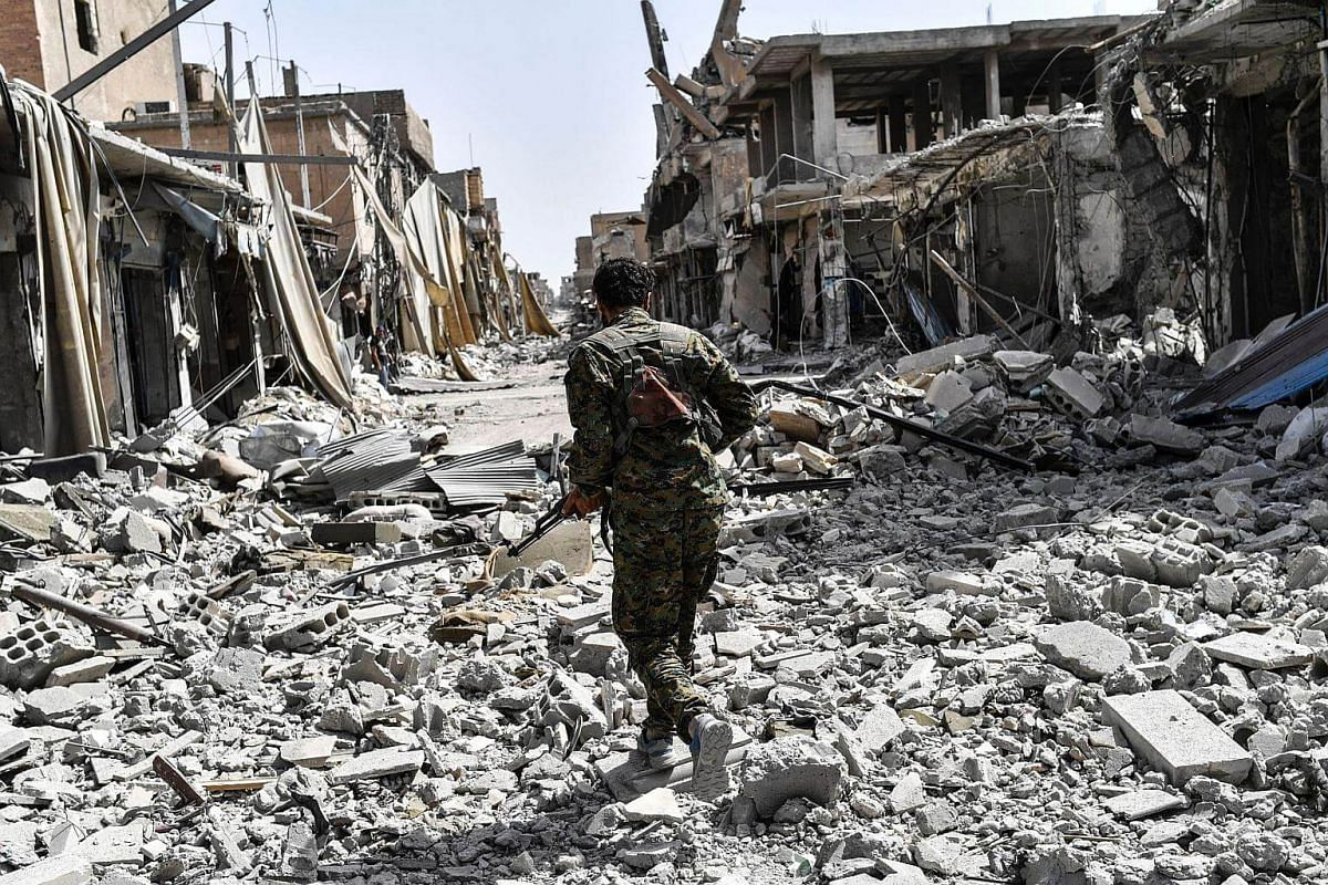 A member of the Syrian Democratic Forces sprints through the debris in the old city centre on the eastern frontline of Raqa on Sept 25, 2017.