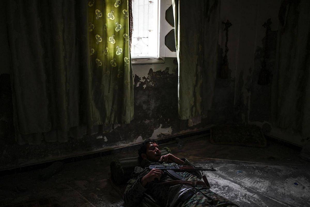 A member of the Syrian Democratic Forces sleeps inside a building on the eastern frontline of Raqa on Sept 24, 2017.