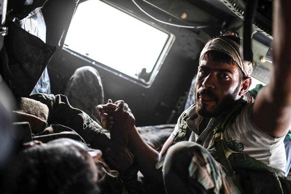 A member of the Syrian Democratic Forces comforts his wounded comrade Ibrahim who was shot by a sniper as they drive towards a medical centre on the eastern frontline of Raqa on Sept 24, 2017.