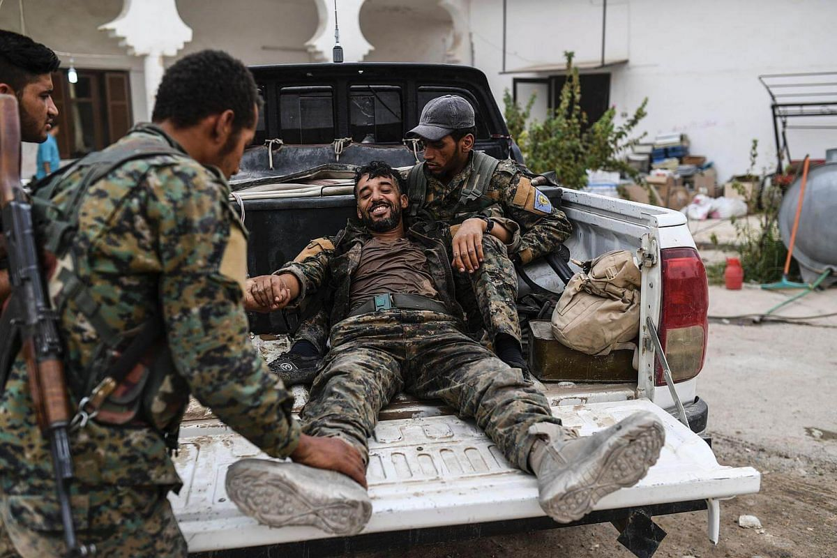 A heavily wounded member of the Syrian Democratic Forces smiles as he arrives at a medical centre on the eastern frontline of Raqa on Sept 24, 2017.