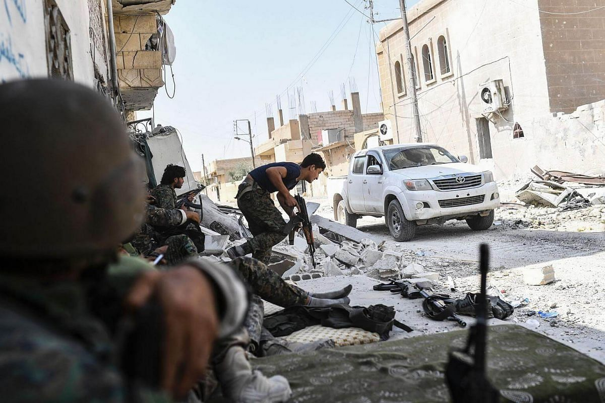 Syrian Democratic Forces take position following a sniper shot in their direction on the eastern frontline of Raqa on Sept 24, 2017.