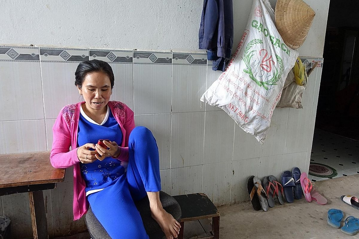 VIETNAM A migrant family relaxing outside their room in the village. The rooms in urban lodgings for migrants tend to be cramped and squalid, giving communal spaces an added importance. Migrant worker Vo Thi Kim Phuong getting some air outside her wi
